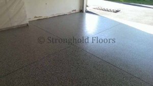 Saw cut joints in the concrete garage floor highlights the epoxy coatings.